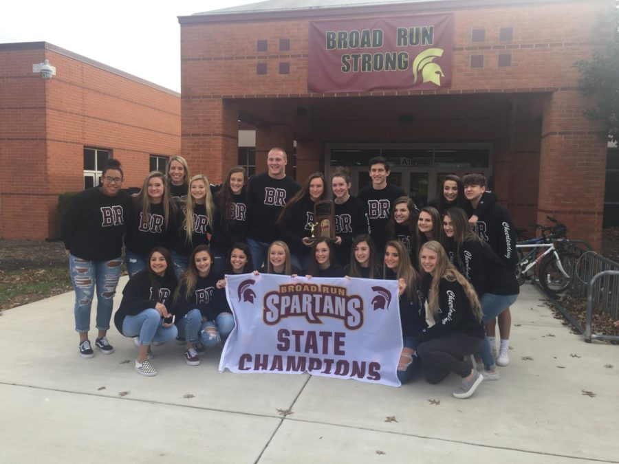 The 2018 Varsity Cheer Team holding their state championship trophy and banner.