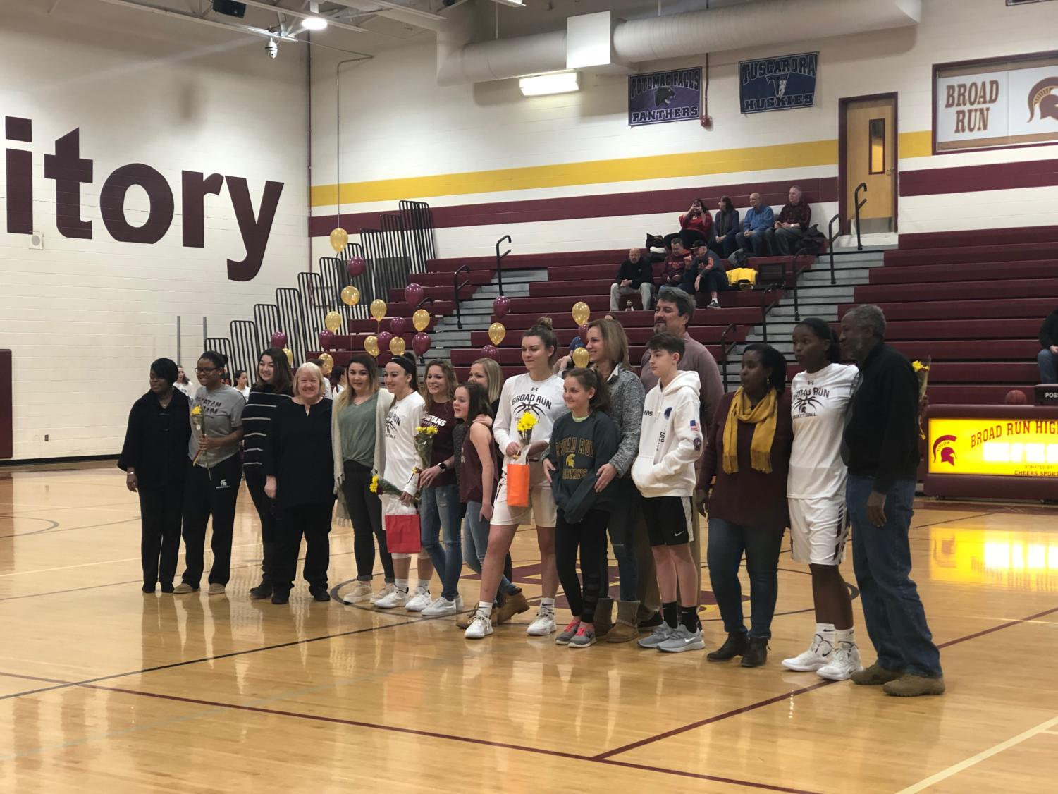 Families and students gather on the court for Senior NIght.